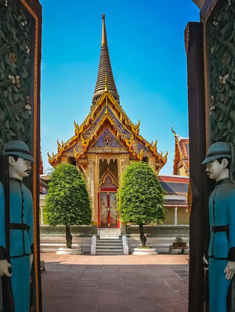 Soldiers sculptures guarding open gates to the Buddhist temple in Bangkok, Thailand, Asia Stock Photo