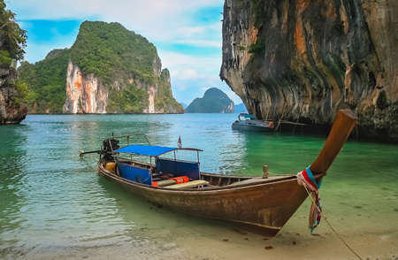Wooden boat boat moored on a small beach in a beautiful cove among the impressive karst formations on the coast of Thailand