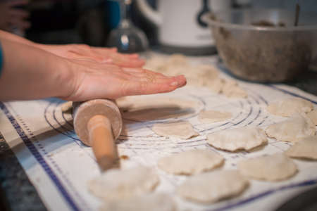 Close up of woman hands holding rolling pin and preparing traditional polish christmas dish called pierogi, dumplings filled with mushroom and onion filling Stock Photo