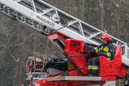 Karpacz, Poland -  February 2018 : Firefighter sitting in control chair operating an extendable crane arm with his colleagues in it cutting branches of a tree after heavy snowfall