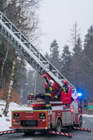 Karpacz, Poland -  February 2018 : Firefighters in action on a fire engine with the extendable crane cutting branches of a tree for safety reasons after heavy snowfall