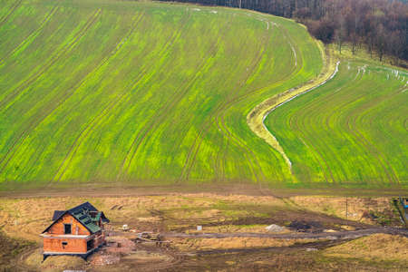 Aerial view of an unfinished house and green empty field in winter among the rural landscape of Lower Silesia, Poland.
