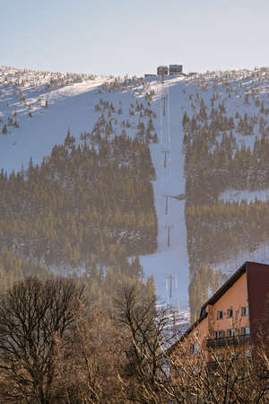 Ski lift to the top of Kopa mountain on a sunny winter day as seen from Karpacz ski resort, Poland Stock Photo