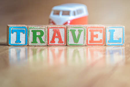 Small toy car on the floor in the living room in the house next to the wooden letter blocks spelling the word travel
