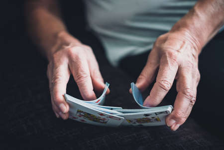 Senior mature woman reaching for the card on top of the deck while playing at home
