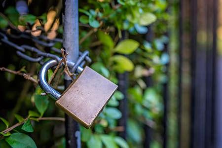 Metal padlock hanging on the black rusty metal fence