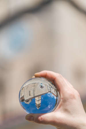 Saint Nikola Church tower reflected in a glass ball held by a tourist, Perast, Kotor harbor, Montenegro Stock Photo