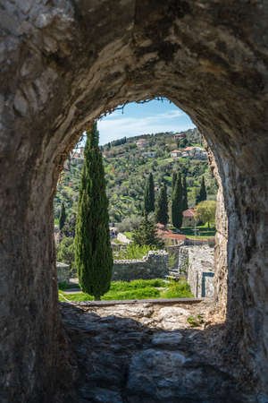 Arched wall window view of the ruins of the old citadel and city walls in Stari Bar town near Bar city, Montenegro