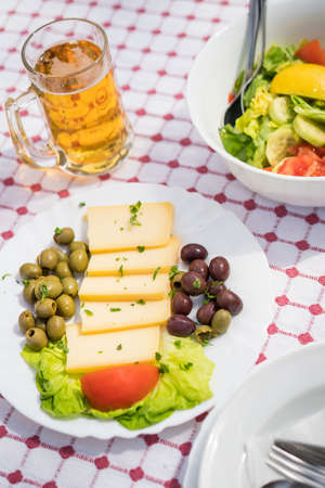 Summer salad with olives, tomatoes and cheese as a starter before the main course on table outside the restaurant