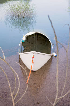 Lonely empty white fisherman boat on the shore of lake Skadar in Virpazar, Montenegro Stock Photo