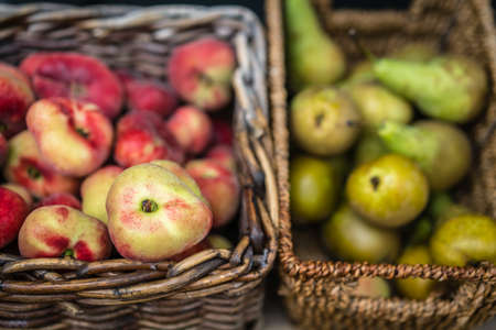 Nectarines and pears in wicker basket on display on a stall at farmers market in Cornwall, Uk Archivio Fotografico