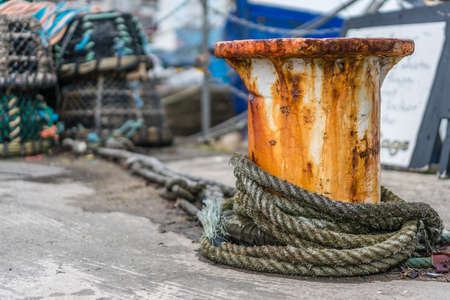 Bollard with a chain and a rope in a port dock
