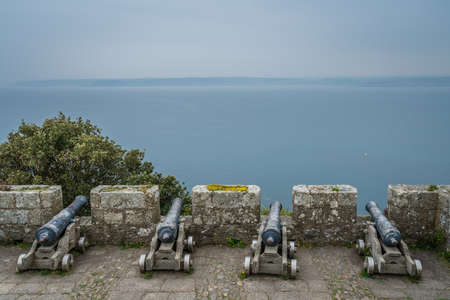 Four large brass cannons on the external defensive walls of St Michaels Mount fortress, Marazion near Penzance, Cornwall, UK