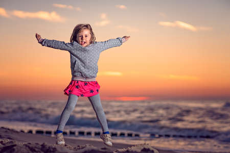 Cute little Caucasian girl jumping high on the beach at sunset in summer