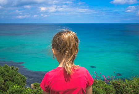 Little girl dressed in red t-shirt standing on a small cliff and admiting stunning Cornish coastline near St. Ives in Cornwall, England, UK