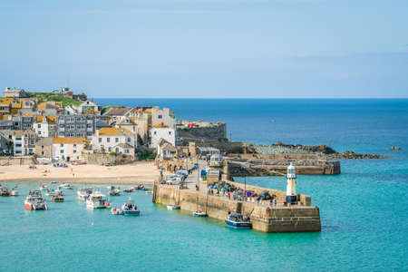 St. Ives, England - June 2018 : Small lighthouse at the entrance to the port in Saint Ives, Cornwall, UK