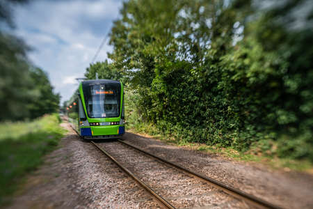 London, England - July 2018 : Modern tramway on tracks going through the forest Editorial