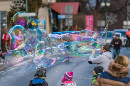 Karpacz, Poland - February 2018 : Man releasing giant soap bubbles for children to catch on the main high street in Karpacz town, polish winter ski resort