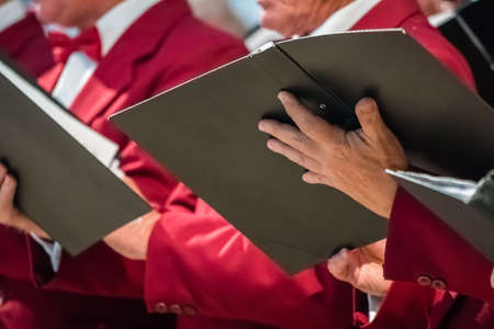 Close up of mens choir members holding singing book while performing in a cathedral in Rochester, Kent, UK Stock Photo