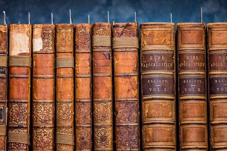 Rangée de livres anciens à couverture rigide et souple sur étagère dans une bibliothèque