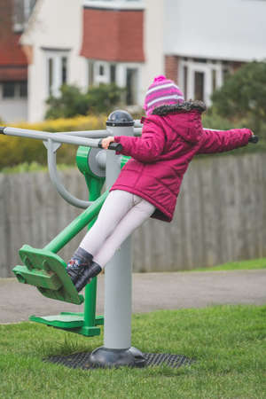 Little Caucasian girl exercising on the outdoor training machine on a chilly autumn day