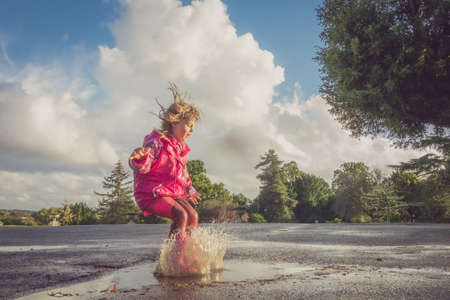 Little Caucasian girl jumping into the puddle after rain in english countryside