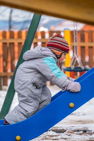 Young little boy climbing up the blue slide on the outdoor playground in cold winter
