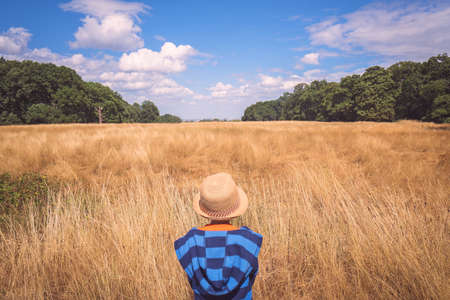 Little boy wearing straw hat standing in front of a yellow grass field