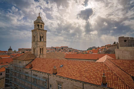 Church bell tower and rooftop of an old house in Dubrovnik, viewed from the Old Town fortified walls, Croatia