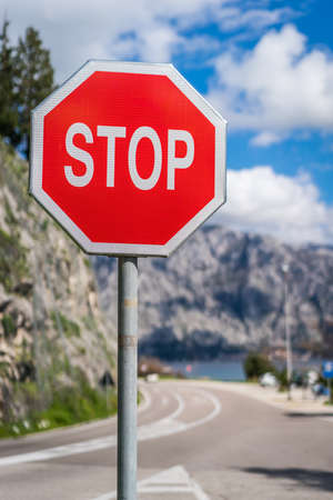 Red Stop sign on the road in Montenegro Фото со стока