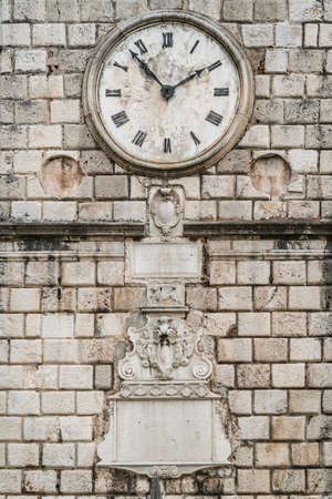 The close up of the Clock on the facade of the Tower on the Square of Arms in the Old Town of Kotor in Montenegro