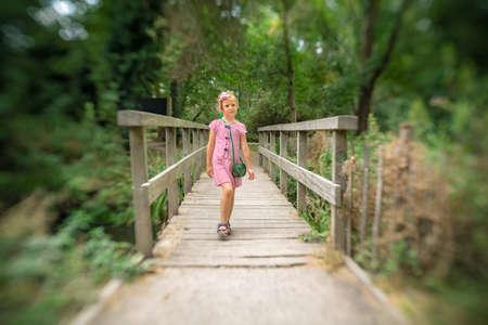 Cute little Caucasian girl crossing small wooden bridge in a public park in summer