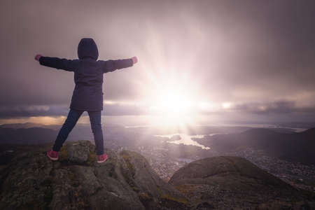 Victorious girl on top of the Mount Ulriken, Bergen, Norway