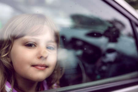 Cute little Caucasian girl sitting inside the car and looking through the window