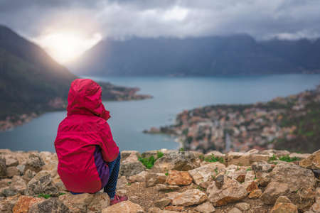 Girl in a waterproof red jacket sitting on the viewpoint and admiring stunning landscape of the Bay of Kotor, Montenegro