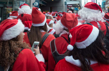 London, UK - December 2018 : Group of people dressed in santa outfits and taking part in a themed SantaCon event Stock Photo - 119557736