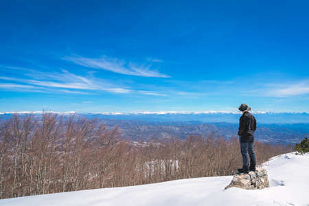 Male tourist taking wearing a hat standing on a rock and admiring the stunning mountain winter landscape panorama as seen from the top of Mount Lovcen in Lovcen National Park, Montenegro