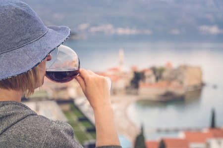 Caucasian woman wearing blue hat standing in an apartment balcony and holding glass with red wine looking at the Budva town below, Montenegro Imagens