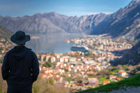 Tourist with a hat admiring the stunning landscape of the Bay of Kotor in Montenegro as seen from the road to Lovcen National Park