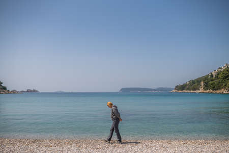 Blond Caucasian female tourist walking slowly on the beach and admiring the stunning Croatian coast in Dubrovnik