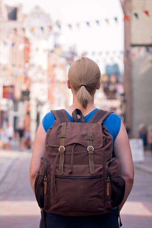Blond Caucasian female standing on a high street in an English town carrying small brown retro backpack Foto de archivo