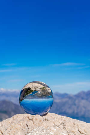 Stunning landscape of the Bay of Kotor and Lovcen National Park in Montenegro reflected in a large glass ball placed on a large boulder