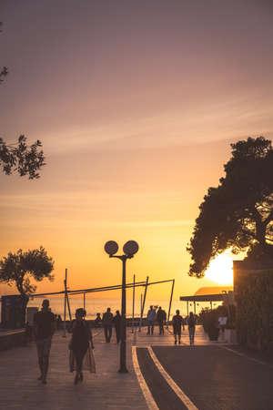 Dubrovnik, Croatia - April 2018 : People walking on a seafront promenade at sunset in Dubrovnik suburb of Lapad