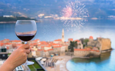Woman holding glass with red wine on the balcony of her apartment in the Budva town, Montenegro 写真素材