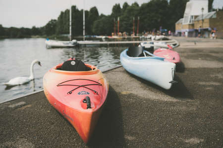 London, England - July 2018 : Three kayaks on the shore of a small lake in summer in Wimbledon Park Editorial