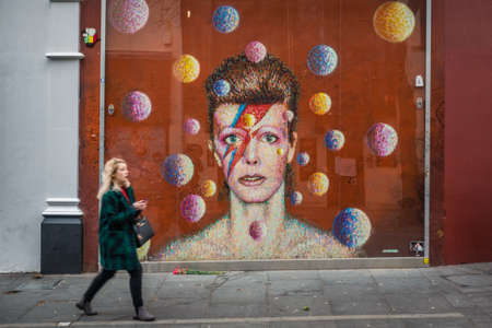 London, England - December 2018 : Woman walking in front of the graffiti in memory of singer David Bowie as Ziggy Stardust, Brixton