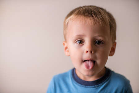 Portrait of a cute naughty and mischievous Caucasian boy sticking his tongue out