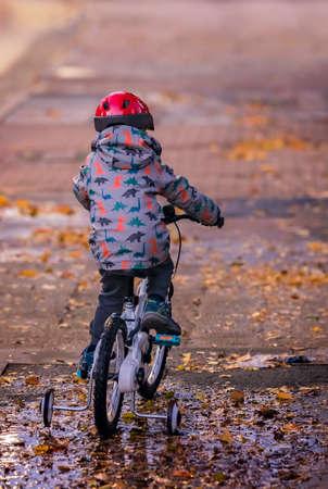 Kleiner Junge mit rotem Schutzhelm, der abends nach Regen auf einem Fahrrad fährt