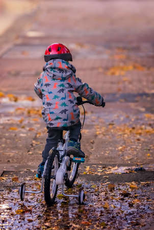 Little boy wearing red protective helmet riding on a bicycle in the evening after rain
