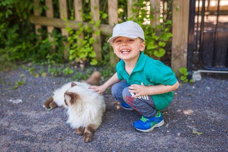 Porträt eines glücklichen kleinen Jungen, der Katzenfell auf dem Bauernhof streichelt